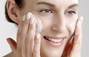 Kvinna som applicerar rengöringsgel i ansiktet.
