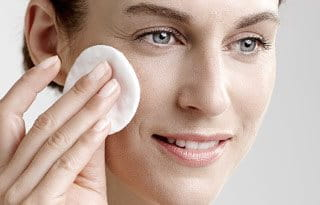Woman applies toner with cotton pad.