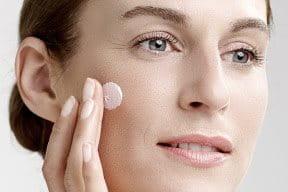 Una mujer aplicándose cuidados en las mejillas.