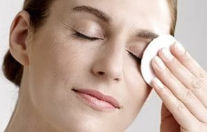 Femme se démaquillant les yeux avec un coton