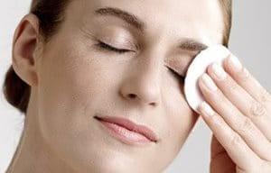 Žena skida šminku sa očiju pomoću pamučnog tupfera.