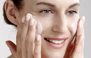 Una mujer se aplica emulsión en la cara.