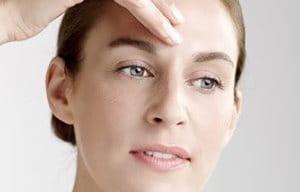 Frau trägt Konzentrat auf ihrer Stirn auf.