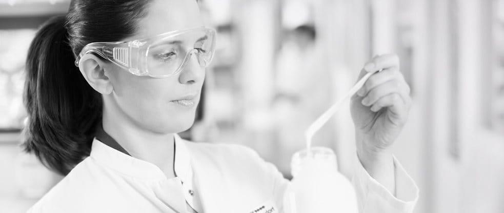 Een vrouwelijke wetenschapper met veiligheidsbril bezig met het testen van een formule.
