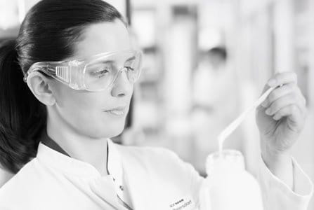 Female scientist with safety goggles testing a formula