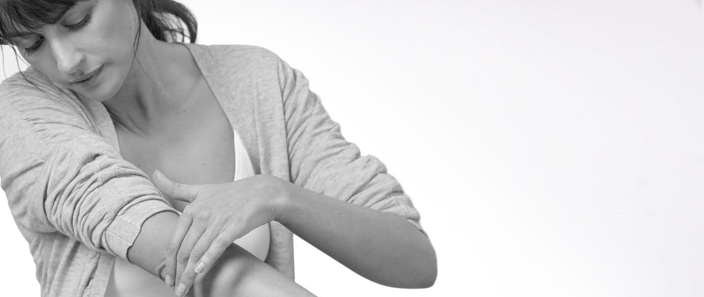 Жінка із сухою та тріснутою шкірою на лікті