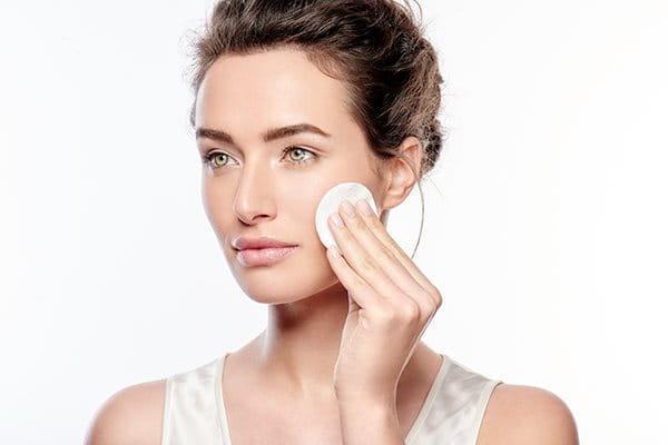 Nainen pyyhkii kasvojaan kasvovedellä