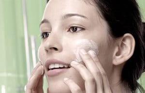 Mujer aplicándose un limpiador en las mejillas
