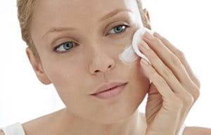 Une femme applique la lotion sur le visage