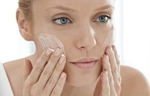 Una mujer aplicándose limpiador en el rostro