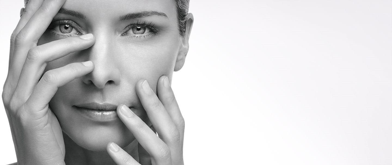 Sieviete, kura ar rokām ir daļēji aizsegusi seju.