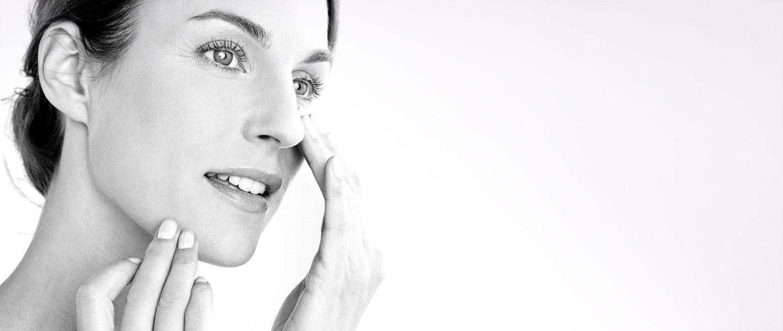 Una mujer aplicándose crema en la mejilla derecha.