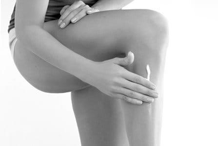 Woman touching her left leg