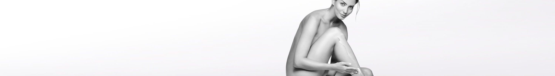 Gola žena oslanja se laktom na koljeno