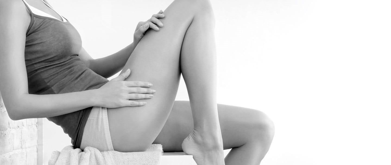 Mulher aplicando produto Eucerin na perna