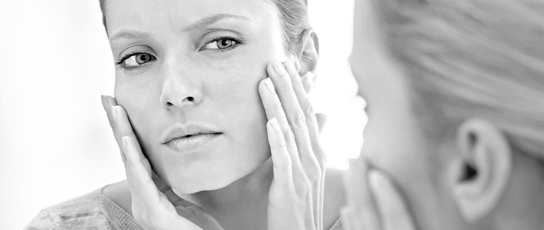 Donna con la pelle ipersensibile che si guarda allo specchio