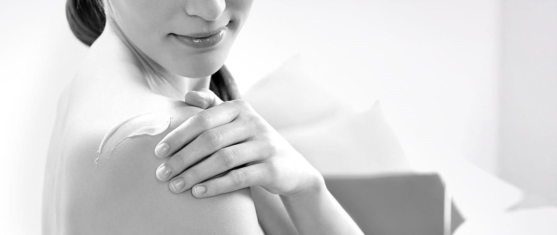 Mujer aplicándose loción en el hombro