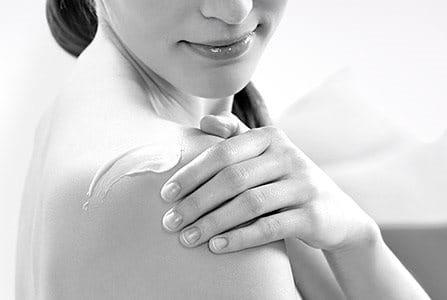 Woman applying cream on her shoulder.