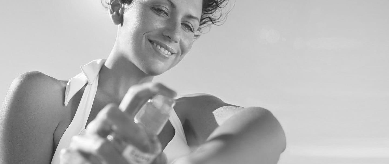 Mujer aplicándose un  filtro solar en el brazo