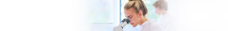 Frau schaut durch Mikroskop