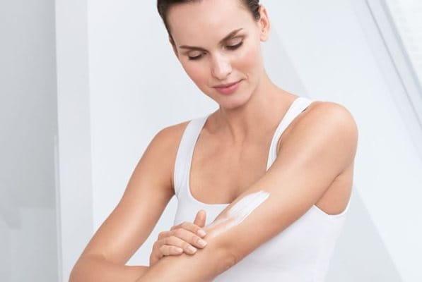 Frau mit Keratosis pilaris cremt sich den Arm ein