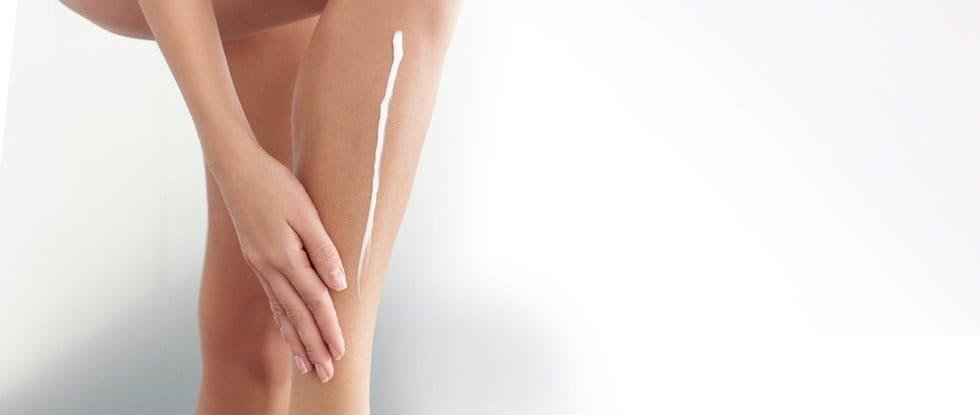 Frau trägt Creme auf ihr rechtes Bein auf.