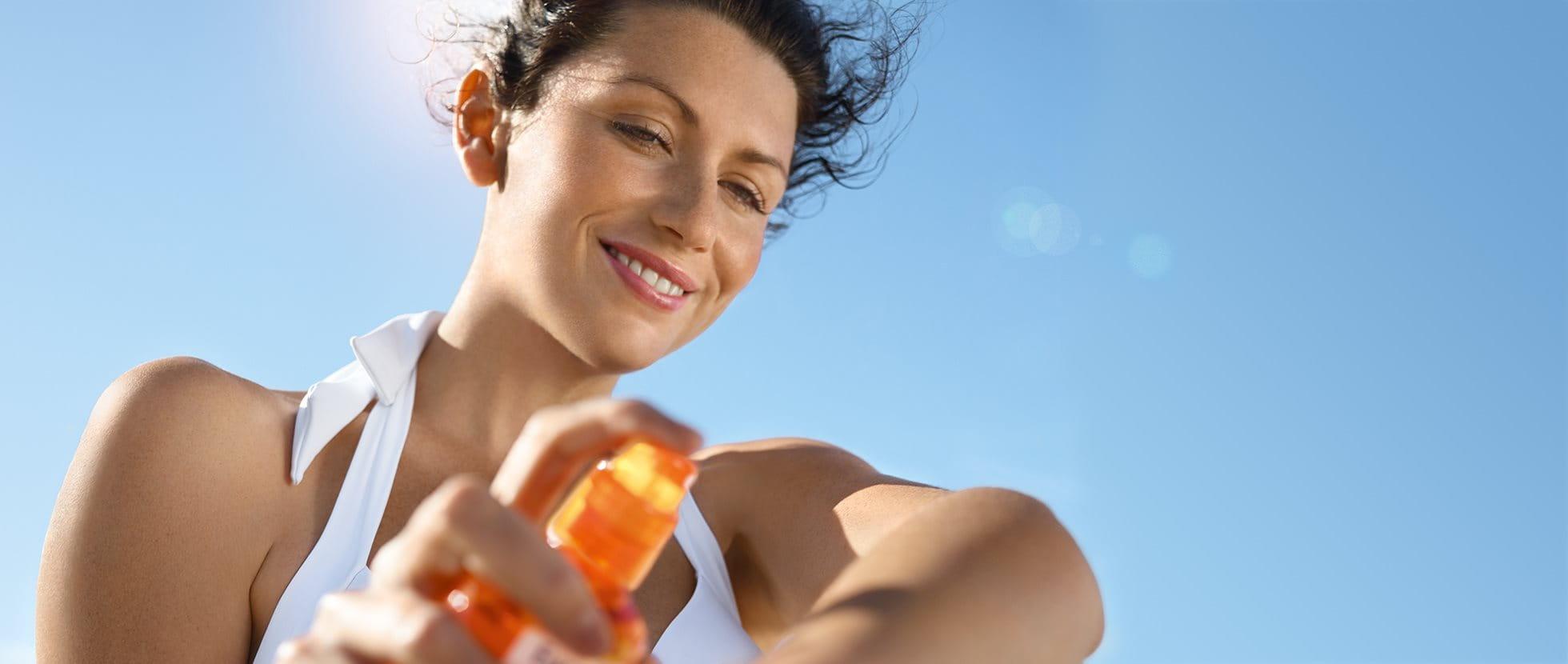 Frau trägt Sonnenschutzmittel auf ihren Arm auf.