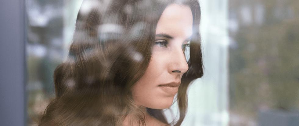 Žena gleda kroz prozor