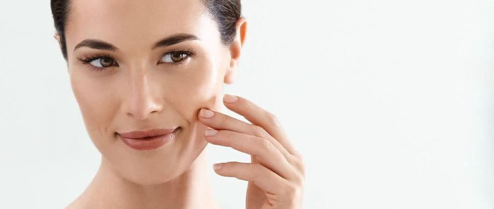 Žena nanosi kremu na obraz.
