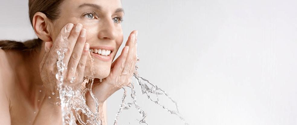 Žena pere svoje lice.