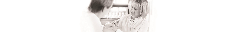 Cientista feminina a aplicar creme nas costas da mão - um cientista masculino está a olhar.
