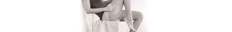 Mulher a aplicar um produto Eucerin na perna.