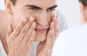 En kille tvättar ansiktet.